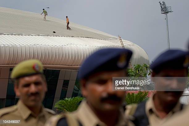 Indian police stand guard as labourers walk on top of the weightlifting venue for the approaching 19th Commonwealth Games 2010 Delhi at Jawaharlal...