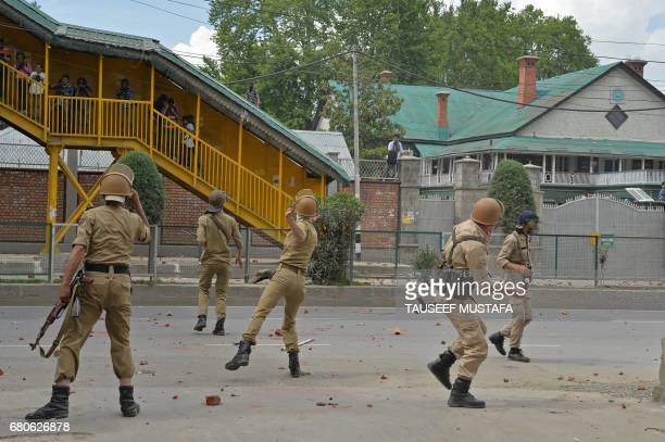 Indian police through stones towards Kashmiri students during clashes in central Srinagar's Lal Chowk on May 9, 2017. Police fired into a crowd of...