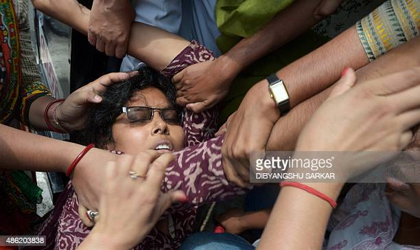 Indian police try to drag a leftist activist into a police van as she faints on the road during a protest in Kolkata on September 2 2015 Millions of...