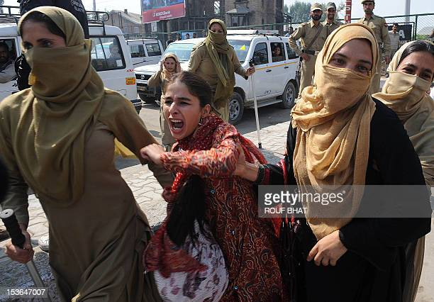 Indian police women detain Kashmiri volunteers from the National Youth Corps as they shout antigovernment slogans during a protest march towards the...