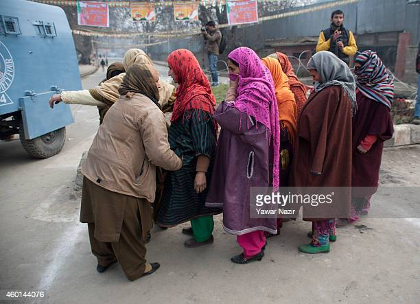 Indian police women frisk a Muslim women supporters of Indian Prime Minister Narendra Modi's outside the venue where Modi is addressing his maiden...