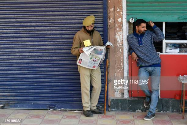 A Indian policeman reads newspaper during shutdown in Srinagar Jammu and Kashmir on 31 October 2019 Kashmir valley shutsdown for 88th consecutive day...
