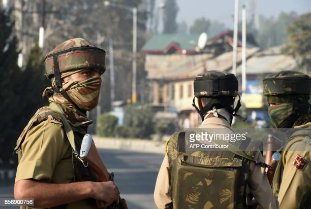 Indian policeman stands guard near the site of gunfight between suspected militants and Indian government forces in Srinagar on October 3 2017...