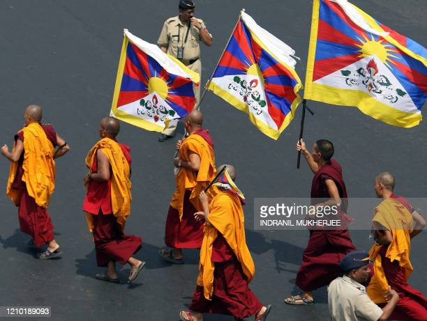 Indian policeman watch Tibetan monks on a protest march in Mumbai on April 10 2008 Tibetans in exile under the banner of Tibetan Solidarity Committee...