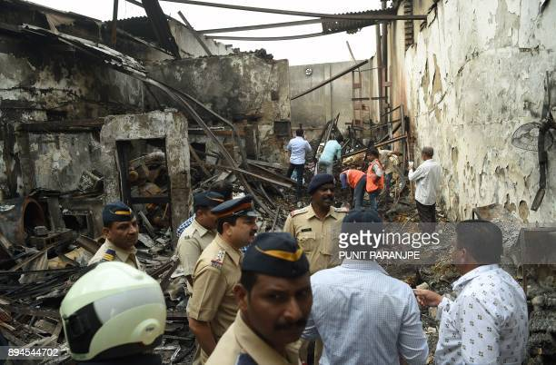Indian policemen and local authority officials inspect the scene of a fire in Mumbai on December 18 2017 Fire tore through a sweet shop in the Indian...