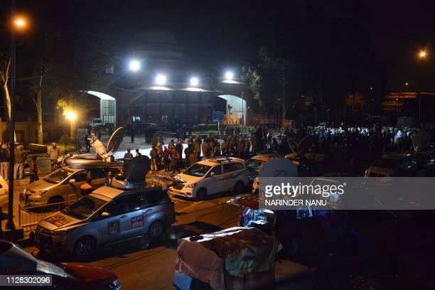 Indian policemen and media personnel wait for the return of Indian pilot Indian Air Force Wing Commander Abhinandan Varthaman outside the Integrated...