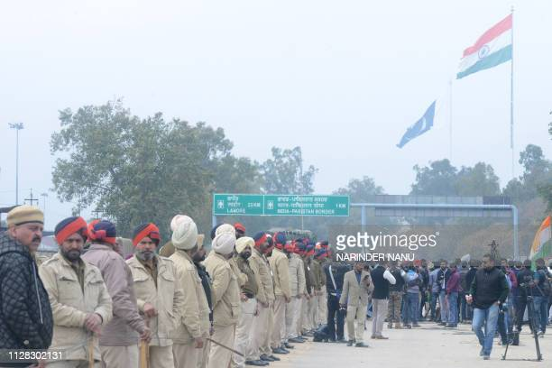Indian policemen and media personnel wait for the return of Indian pilot Indian Air Force Wing Commander Abhinandan Varthaman at the IndiaPakistan...