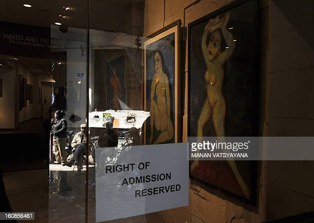 Indian policemen are reflected in the glass door during an art exhibition The Naked and the Nude at an art gallery in New Delhi on February 7 2013...
