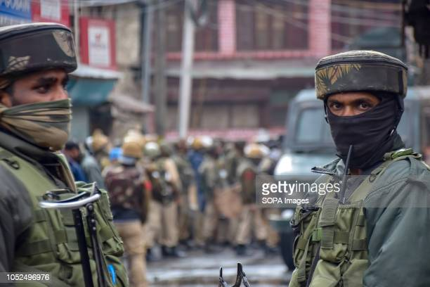 Indian Policemen are seen on guard outside the house where suspected militants were hiding during a gun battle with government forces that killed at...