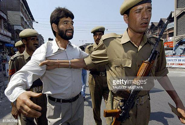 Indian policemen arrest an activist of the Jammu and Kashmir National Front during a protest to demand the release of separatist leader Nayeem Khan...