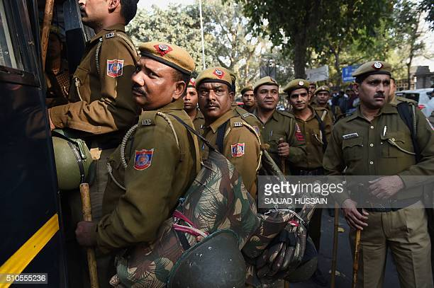 Indian policemen board a police bus following a protest outside the office of the Indian Minister of Human Resource Development Smriti Irani against...