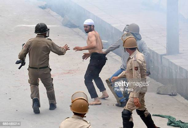 Indian policemen detain a youth during clashes in Srinagar the summer capital of Indian controlled Kashmir on May 19 2017Indian police later used...