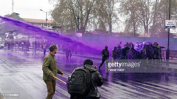 Indian policemen fire purple colored water from a water canon on Kashmir government employees during a protest on April 06 2011 in Srinagar in Indian...