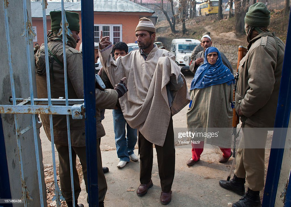 Indian policemen frisks Kashmiri Muslim village heads before entering a polling station during state's legislative council election on December 03, 2012 in Budgam, west of Srinagar, Indian Administered Kashmir. Village heads in Indian-administered Kashmir voted for their representatives in the state's legislative council for the first time in 38 years. These grass root workers are represented by four people in the council- the lower house of Kashmir assembly. Inthe past year the village heads have been attacked by unidentified gunmen in the conflict torn region, with many resigning from their post after at least 10 village heads were killed. Today's polling saw long queues despite the resistance leadership calling for a boycott. But the biggest militant group in the region, the Hizbul Mujahideen, had refrained from calling a boycott saying the polling was necessary for daily administration of the state.