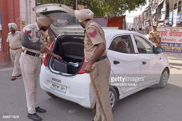Indian policemen inspect a car during a strike call by Sikh radical groups on the occasion of the 32nd anniversary of Operation Blue Star in Amritsar...