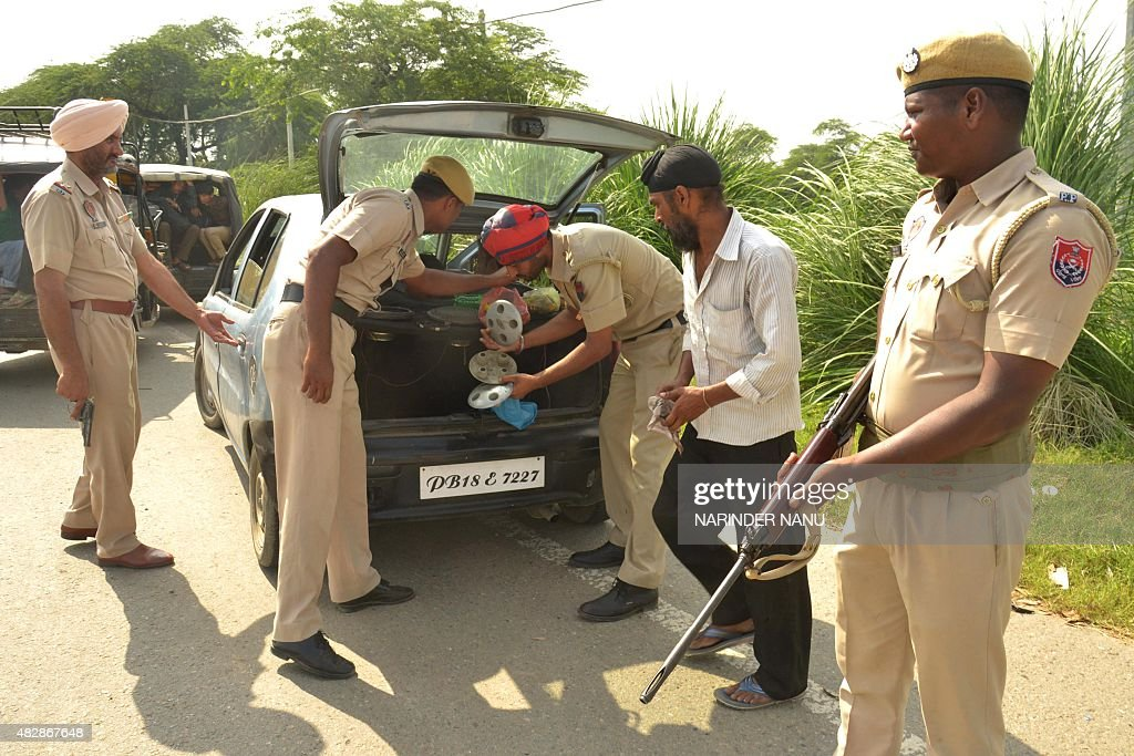 Indian policemen inspect a car in Amritsar near the Wagah border post between India and Pakistan on August 3 2015 Security has been increased around..