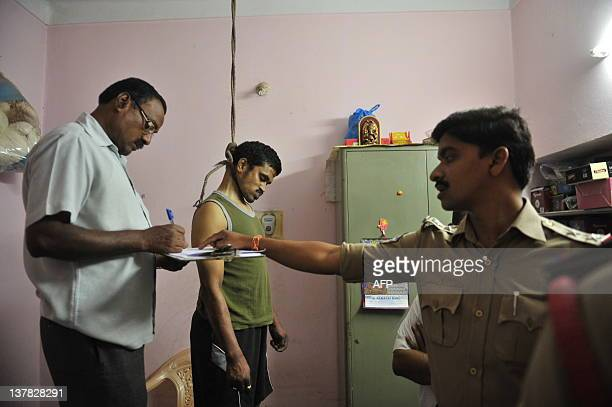 Indian policemen investigate as the dead body of Balaji hangs after he committed suicide in his house in Hyderabad on January 28 2012 Four people of...