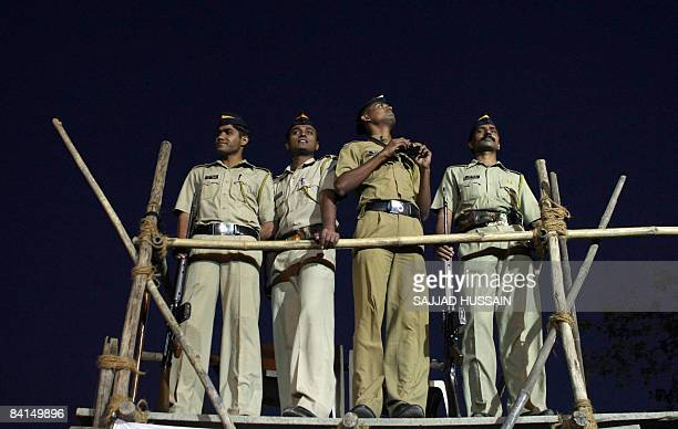 Indian policemen keep vigil on a watchtower near the unseen Gateway of India monument during New Year's Eve in Mumbai on December 31 2008 India...
