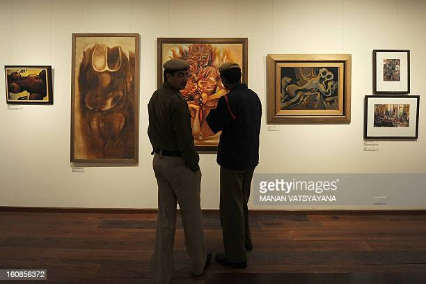 Indian policemen look at paintings during an art exhibition The Naked and the Nude at an art gallery in New Delhi on February 7 2013 Earlier this...
