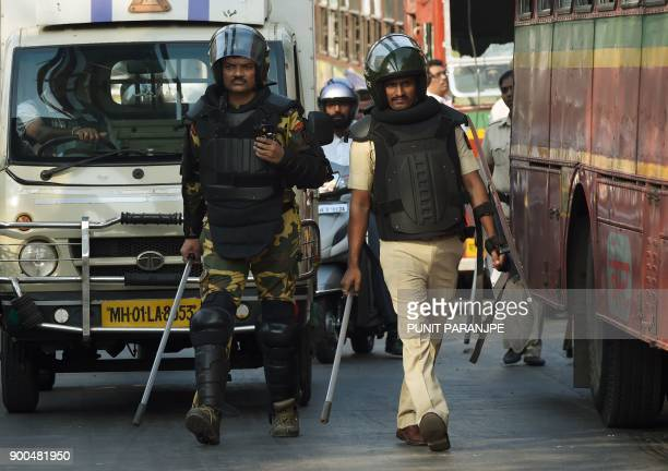 Indian policemen patrol along a road after supporters of the Republican Party of India turned violent during a protest in Mumbai on January 2 2018...