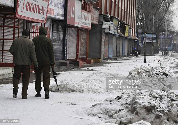 Indian policemen patrol in a desert street during a one day strike in Srinagar on January 26, 2012 during the Republic Day celebrations. A...
