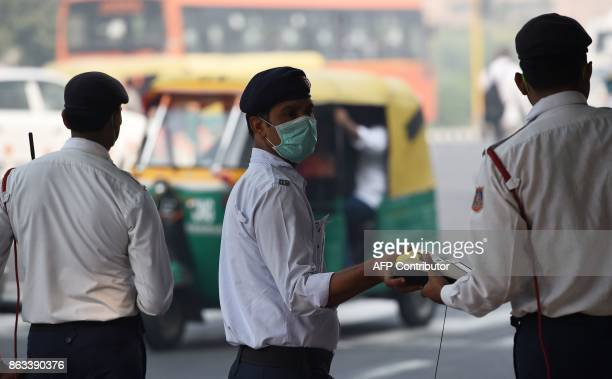 Indian policemen protects their faces with masks amid heavy smog in New Delhi on October 20 2017 the day after the Diwali Festival New Delhi was...