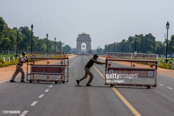 Indian policemen push barricades to place them in the center of a a road leading to historic India Gate during a oneday nationwide Janata curfew...