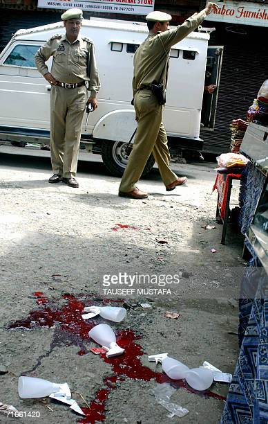 Indian policemen secure the area around a bloodstained pavement at Kukar Bazar in Srinagar, 17 August 2006, following an attack by suspected Islamic...