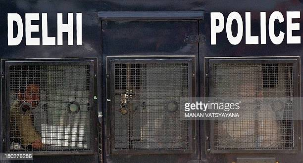 Indian policemen sit in the back of the vehicle believed to be carrying the accused in a gang rape and murder case as it arrives at the Saket Court...