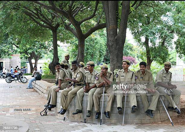 Indian policemen sit under a tree as they take rest near the bomb blast site inside the Lumbini Park in Hyderabad 26 August 2007 Indian security...