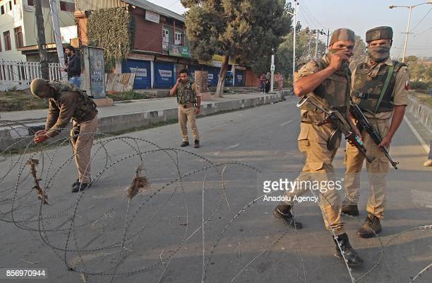 Indian policemen stand alert in Humhama on the outskirts of Srinagar the summer capital of Indian controlled Kashmir on October 03 2017 Three suicide...
