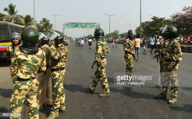 Indian policemen stand guard after Republican Party of India supporters blocked traffic on the Eastern expressway during a protest in Mumbai on...