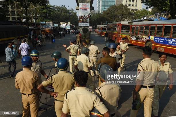 Indian policemen stand guard at a junction after supporters of the Republican Party of India turned violent during a protest in Mumbai on January 2...
