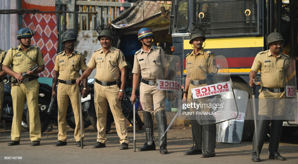 Indian policemen stand guard during Republican Party of India (RPI) supporters protest in Mumbai on January 3, 2018. India's Republican Party supporters took part in a protest all over the city on January 3, after the death of a young Dalit activist in Maharashtra's Pune district following an altercation between two groups during celebrations to mark the bicentenary of a British-Peshwa war. /