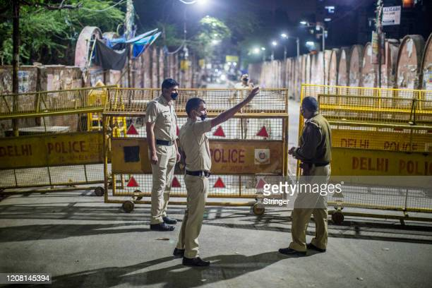 Indian policemen stand guard on a deserted commercial hub as they enforce a lockdown order by Delhi's government as a preventive measure against the...