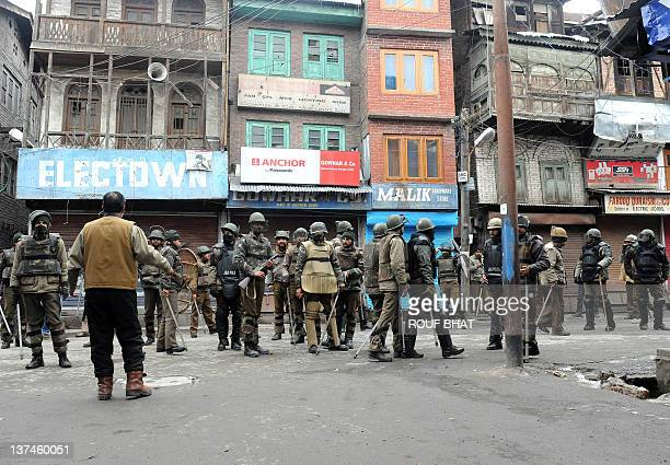 Indian policemen stand guyard during a protest by activists of the Hilal War political party in Srinagar on January 21 2012 The political party...