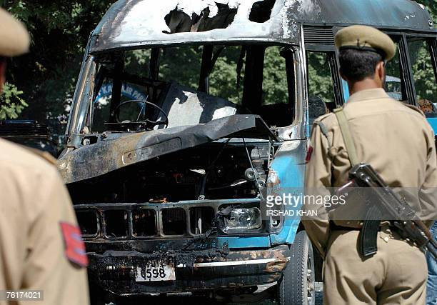 Indian policemen stand near a fire damaged police vehicle in Srinagar 19 August 2007 after it was set ablaze by an irate mo The police vehicle was...