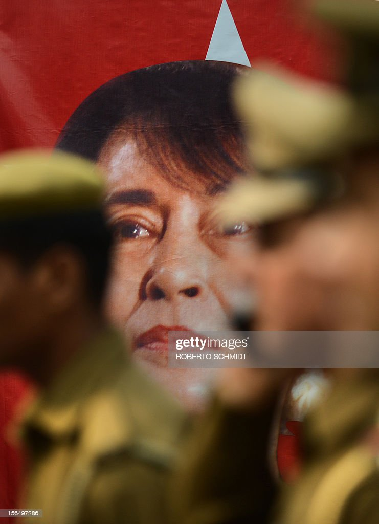 Indian policemen stand near a poster bearing a portrait of Myanmar opposition leader and National League for Democracy Chairperson Aung San Suu Kyi near the entrance of a school in New Delhi on Nov...