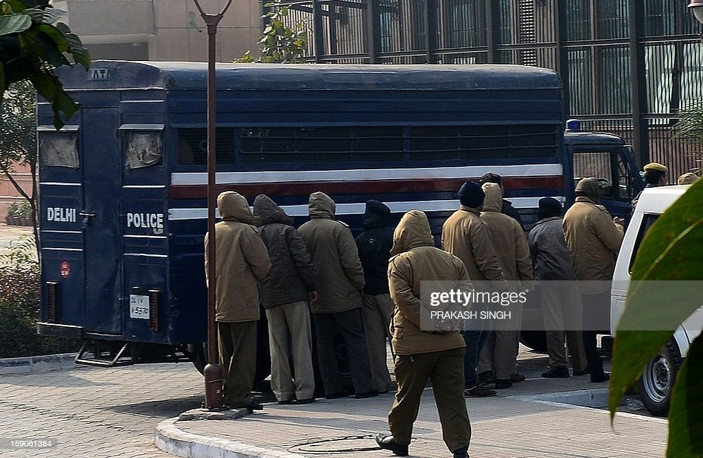 Indian policemen stand next to a prisoner transport vehicle moments after it arrived under heavy security at the Saket District Court in New Delhi on January 7, 2013 prior to the hearing of a gang rape and murder case. Five men accused of gang-raping and murdering a 23-year-old student in New Delhi made their first appearance in court on Monday where they were informed of the full list of charges, a magistrate said. AFP PHOTO/ Prakash SINGH