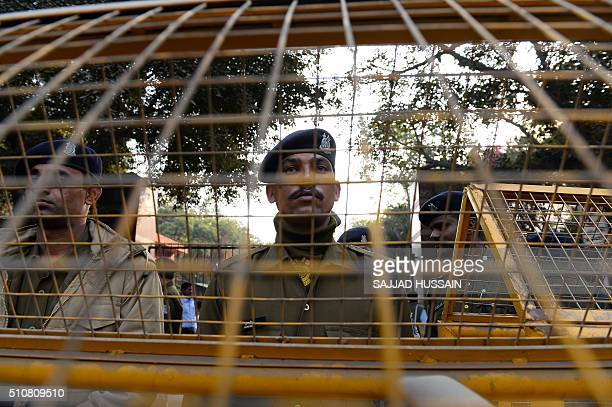 Indian policemen stands guard at the main gate of Jawaharlal Nehru University during a protest in New Delhi on February 17 2016 An Indian student...