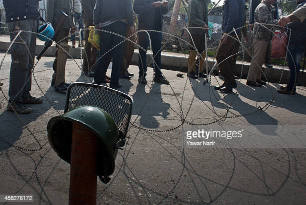 Indian policemen stop kashmiris from crossing concertina razor wire as they try to reach to the city centre during restrictions on a Muharram...