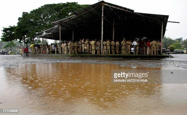 Indian policemen take shelter from the rain under a makeshift canopy as they report for duty at the JawaharLal Nehru Stadium in Kochi 01 October 2007...