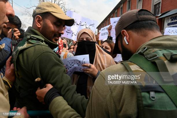 Indian policemen try to stop Pakistani women married to former Kashmiri militants during a protest urging Indian and Pakistani Prime Ministers to...