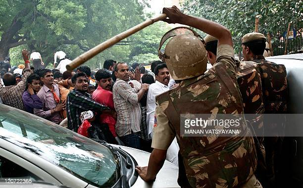 Indian policemen use sticks to beat Bharatiya Janta Party Youth Wing activists during a protest in New Delhi on August 9 2011 An antigovernment...