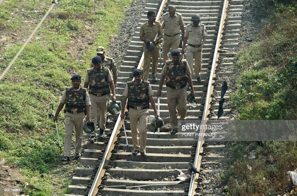 Indian policemen walk along railway tracks during Republican Party of India (RPI) supporters protest in Mumbai on January 3, 2018. India's Republican Party supporters took part in a protest all over the city on January 3, after the death of a young Dalit activist in Maharashtra's Pune district following an altercation between two groups during celebrations to mark the bicentenary of a British-Peshwa war. /