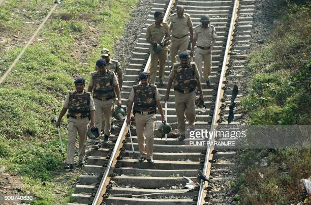 Indian policemen walk along railway tracks during Republican Party of India supporters protest in Mumbai on January 3 2018 India's Republican Party...