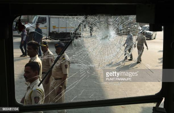 TOPSHOT Indian policemen walk past the broken window of a bus after a Republican Party of India protest turned violent in Mumbai on January 2 2018...