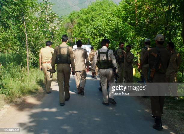 Indian policemen walk towards gunbattle site in the forest area May 24 2013 in Buchoo 40 km south of Srinagar the summer capital of Indian...