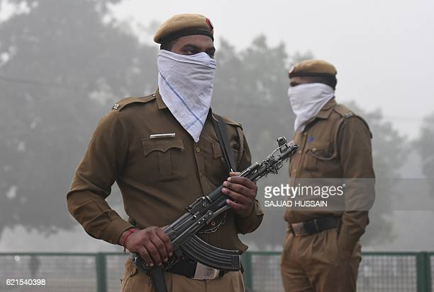 Indian policemen wearing handkerchiefs to cover their face as they patrols near India Gate monument whilst heavy smog covers New Delhi on November 7...