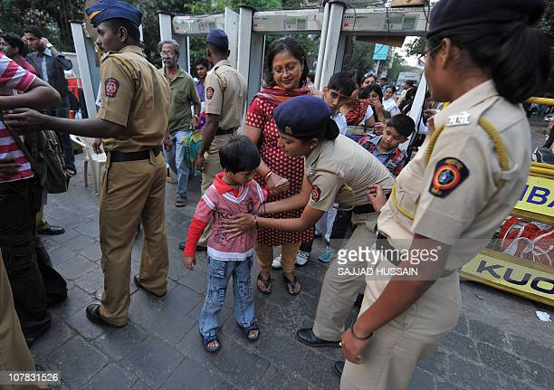 Indian policewomen frisk a child at an entrance checkpoint to the Gateway of India on new year's eve in Mumbai on December 31 2010 Mumbai police...